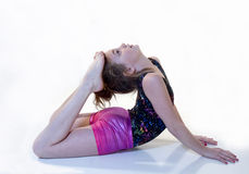 Girl in Back-bend Gymnstic Position. Young girl doing back-bend while bringing her feet to her head in gymnastic position Royalty Free Stock Image