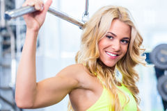 Girl at back fitness training in gym. Girl at back fitness machine training in gym for bodybuilding Stock Photo