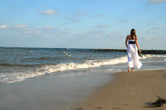 Girl, back, goes on an empty beach Stock Photography