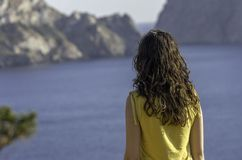 Girl back near sea and island alone. Royalty Free Stock Image