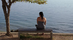 Girl From Back Sitting on Wooden Seat And Looking to Sea Royalty Free Stock Image
