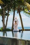 Girl from the back in sport suit is sitting in lotus pose, stretching hands up, meditating on pool on the coast of ocean in Bali stock photos