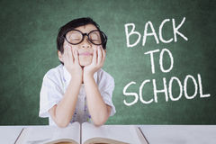 Girl back to school and daydream in the class. Portrait of little girl back to school and daydream in the classroom while wearing glasses with book on the table Royalty Free Stock Images