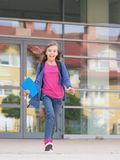 Girl back to school. Happy girl with book and backpack on the first school day. Excited to be back to school after vacation. Full length outdoor portrait stock photos