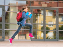 Girl back to school. Happy girl with book and backpack on the first school day. Excited to be back to school after vacation. Full length outdoor portrait royalty free stock photo