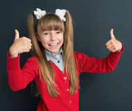 Girl back to school. Happy girl showing thumbs up gesture in front of a big chalkboard. Back to school concept Royalty Free Stock Image