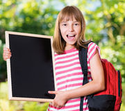 Girl back to school. Outdoor portrait of happy girl 10-11 year old with big alarm clock and backpack. Back to school concept Royalty Free Stock Image