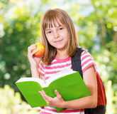 Girl back to school. Outdoor portrait of happy girl 10-11 year old with book and apple. Back to school concept Stock Photos