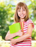 Girl back to school. Outdoor portrait of happy girl 10-11 year old with books. Back to school concept Stock Photo