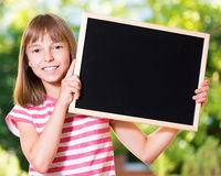 Girl back to school. Outdoor portrait of happy girl 10-11 year old with small blackboard. Back to school concept Royalty Free Stock Image