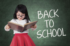 Girl back to school and read a book Stock Photos