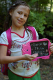 Girl with back to school sign. Cute young girl with rucksack holding black or chalkboard with back to school text; trees in background Stock Photos