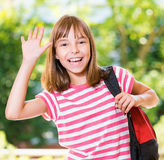 Girl back to school. Smiling girl 10-11 year old stretching her right hand up for greeting .Beautiful schoolgirl with backpack posing outdoors Royalty Free Stock Images