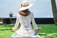 Girl from the back in tunic and summer hat is sitting in lotus pose and meditating on the coast of island on green grass. Woman from the back in tunic and summer stock images