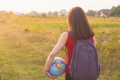 A girl with backback holding globe Stock Photos