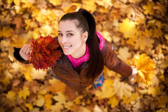 Girl on a background of  autumn leafs. top view Royalty Free Stock Photography