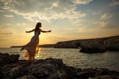 The girl on the background of a beautiful seascape and sunset, silhouette of a girl on a cliff, on a cliff, stock photo
