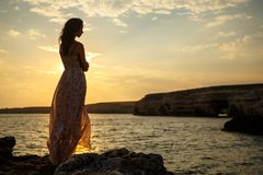 The girl on the background of a beautiful seascape and sunset, silhouette of a girl on a cliff, on a cliff, stock images