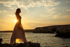 The girl on the background of a beautiful seascape and sunset, silhouette of a girl on a cliff, on a cliff, stock photos
