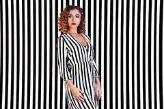 Girl at the background of black and white stripes Stock Images