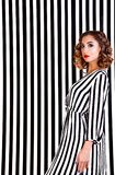 Girl at the background of black and white stripes Royalty Free Stock Image