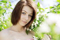 Girl on a background of flowering trees Stock Image
