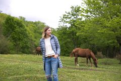 Girl on the background of grazing horses stock photography