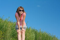 Girl on background of the green herb and sky Stock Images