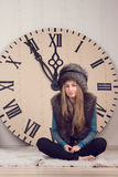 Girl on a background of huge clock Royalty Free Stock Image