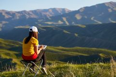 A girl in the background of mountains drawing a landscape. Sits with his back. Painting outdoors. Kazakhstan. Mountain. Spring landscape royalty free stock images