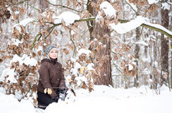 Girl on background of oak leaves in the winter forest. Stock Photo