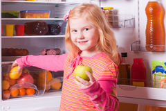 Girl  on background refrigerator Royalty Free Stock Image