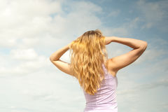 Girl on a background of sky. Beautiful blond girl against the blue sky Stock Images