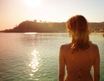 Girl on a background of a sunset over the sea Stock Photos