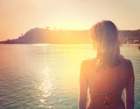 girl on a background of a sunset over the sea Royalty Free Stock Images