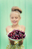Girl on a background of turquoise wall holding plate with cherry. Stock Image