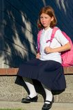 Girl with backpack. Girl sitting on stone bench Stock Image