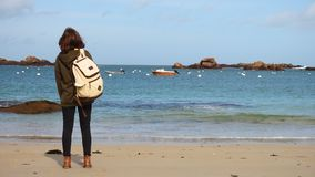 Girl with backpack on a beach. Girl with backpack standing on a beach and looking at the sea stock video
