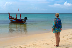 Girl with a backpack on the beach, traditional Thai boat Royalty Free Stock Photography
