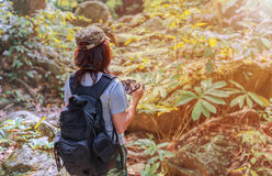 Girl with backpack and camera on trekking trip, standing alone in the trail, enjoying taking photo . Royalty Free Stock Image