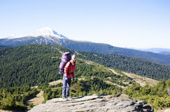 Girl with a backpack climbs the hill. Royalty Free Stock Photos