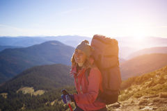 Girl with a backpack climbs the hill. Stock Photos