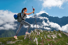 Girl with a backpack climbs on rocky mountain Stock Image