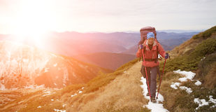 Girl with a backpack climbs to the top of a high mountain. Stock Photos