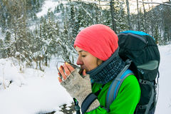 Girl with backpack drinking from a mug of iron in the winter for Royalty Free Stock Photo