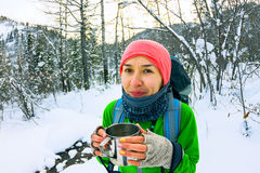 Girl with backpack drinking from a mug of iron in the winter for Royalty Free Stock Images