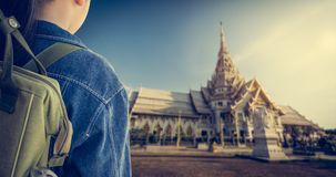 Girl with backpack entering to buddhist temple, Thailand. Stock Photos