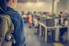 Girl with backpack entering to computer classroom. Stock Image