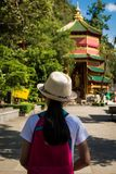 Girl with backpack entering to Quan Yin Shrine. Girl with backpack entering to Quan Yin Shrine at Wat Tham Seua Tham Seua Temple Krabi, Thailand Royalty Free Stock Photos