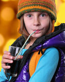 Girl with backpack and hat drinking cola against yellow background Stock Images